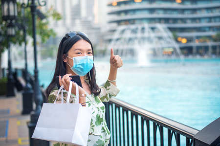 Happy female Asian tourist wearing face mask and taking photo at Dubai mall fountain outdoors. Visiting shopping mall, travel and leisure new normal after coronavirus Covid-19 pandemic lifestyle