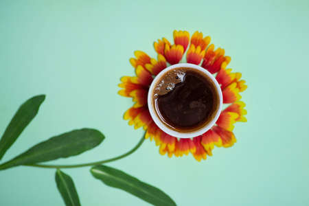 Cup of coffee on top of a cute sunflower and pastel colored background