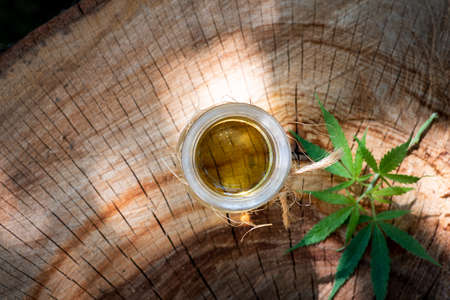 Marijuana oil in a bottle on a wooden log top view with copy space Stok Fotoğraf