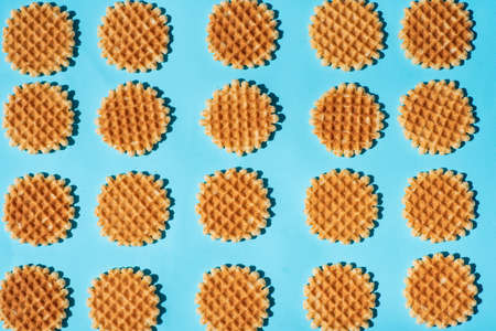 Belgium style homemade waffle dessert on blue background pattern flat lay