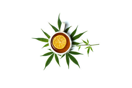 Cup of marijuana infused tea in a cup on top of marijuana leaves isolated top view with copy space Stok Fotoğraf