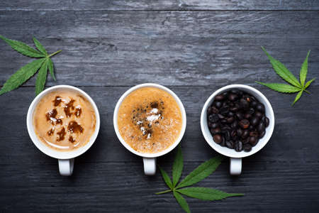 Coffee time. Cup of coffee with cannabis, roasted beans top view with copy space Stok Fotoğraf