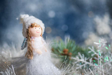 Toy angel and Christmas tree winter holiday festive background and ornaments