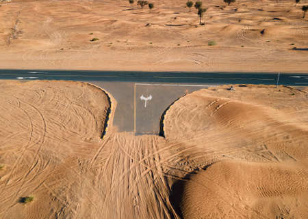 Empty crossroad with sand road meeting the highway in the United Arab Emirates desert aerial view