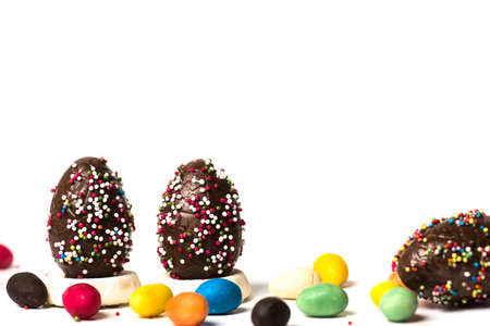 Chocolate Easter eggs with egg candies on white background isolated with copy space Reklamní fotografie