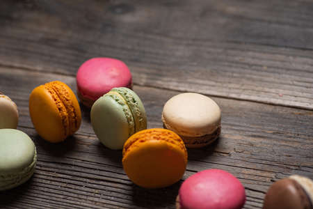 Macaron or macaroon sweet cookie desserts on a wooden table tabletop view