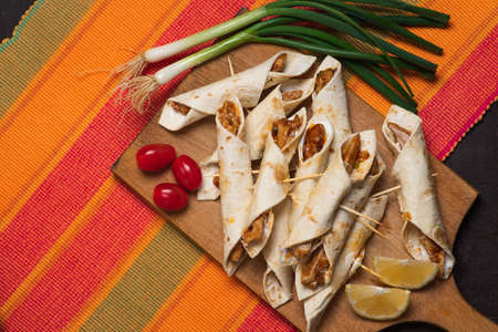 Unbaked small tacos with chicken, dipping sauces and food ingredients called taquitos