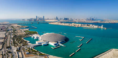 Abu Dhabi, United Arab Emirates - April 6, 2021: Louvre museum and Abu Dhabi aerial cityscape rising from the seaside water at the United Arab Emirates capital at sunrise