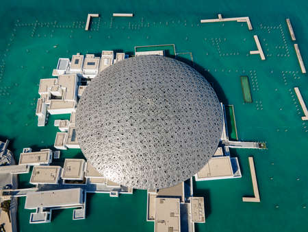 Abu Dhabi, United Arab Emirates - April 6, 2021: Top view of Louvre museum in Abu Dhabi emirate of the United Arab Emirates at sunrise aerial drone view of the building appear to float on the seaside