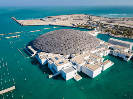 Abu Dhabi, United Arab Emirates - April 6, 2021: Louvre museum in Abu Dhabi emirate of the United Arab Emirates at sunrise aerial drone view of the building appear to float on the seaside