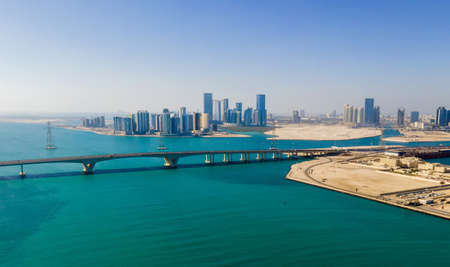 Aerial view of Abu Dhabi skyline rising over the seaside forming modern waterfront of the United Arab Emirates capital city at sunrise Stok Fotoğraf