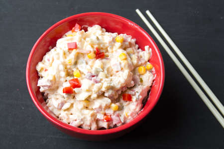 mixed vegetable and mayo salad in a red bowl with chopsticks on a black table