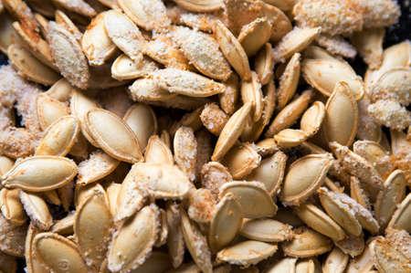 Baked pumpkin seeds covered with salt background Stok Fotoğraf