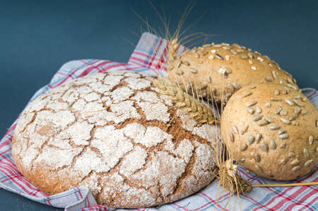 Rye bread loaves and wheat plant on tablecloth
