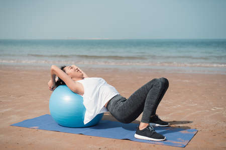 Fit Asian woman exercising on the beach practicing yoga with pilates ball by the seaside for a healthy lifestyle and fit beach body for the summer