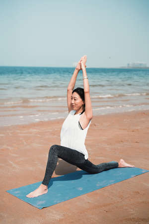 Fit Asian woman exercising on the practicing yoga by the seaside for a healthy lifestyle and fit beach body for the summer Stok Fotoğraf