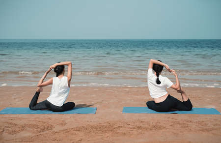 Two unrecognizable woman exercising and practicing yoga on the beach by the seaside. Summer vacation healthy lifestyle for a beach perfect body