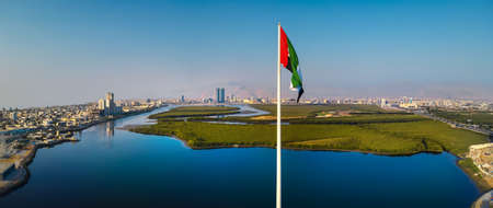 UAE national flag pole and Ras al Khaimah emirate panoramic view in the northern United Arab Emirates aerial skyline landmark and skyline view above the mangroves and corniche downtown area