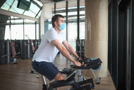 Caucasian man exercising in the gym riding stationary bike indoor cycling. Stok Fotoğraf