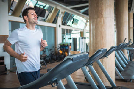 Man jogging on a treadmill during a cardio running warmup exercise in the gym for staying fit and in shape with fitness lifestyle Stok Fotoğraf