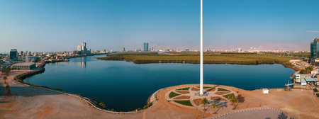 UAE national flag pole and Ras al Khaimah emirate in the northern United Arab Emirates aerial skyline landmark and skyline view above the mangroves and corniche downtown area
