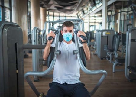 Man exercising in the gym on a pec deck machine for chest and pectoral muscles workout wearing surgical face mask