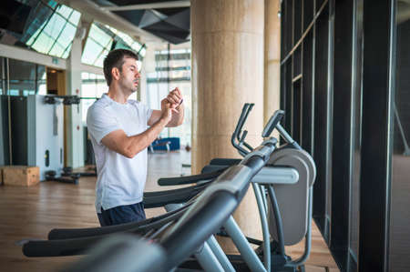 Man using smart watch fitness tracker device while jogging on a treadmill during a cardio running warmup exercise in the gym for staying fit and in shape with healthy lifestyle