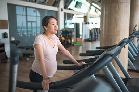 Pregnant Asian woman exercising in the gym indoors walking on a treadmill for a fit and active lifestyle during pregnancy Stok Fotoğraf