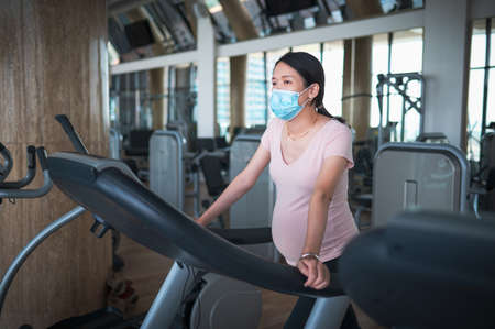 Pregnant Asian woman exercising in the gym indoors walking on a treadmill wearing surgical face mask to prevent virus spread for a fit and active lifestyle during pregnancy Stok Fotoğraf