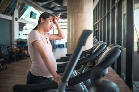 Tired pregnant Asian woman exercising in the gym indoors walking on a treadmill for a fit and active lifestyle during pregnancy