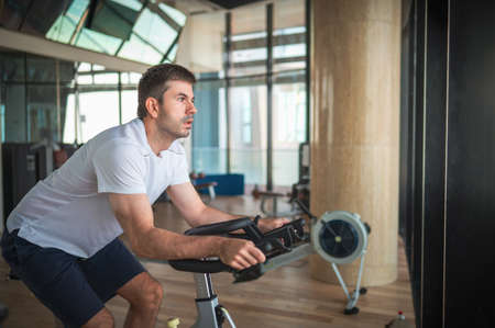 Caucasian man exercising in the gym riding stationary bike indoor cycling. Healthy fitness lifestyle abstract