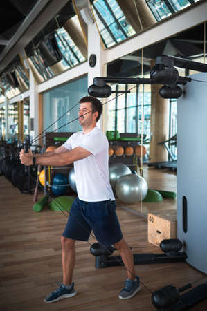 Man exercising in the gym on a pec deck machine for chest and pectoral muscles cable crossover workout