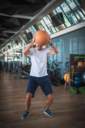 Man exercising in the gym jumping and slamming a heavy medicine slam ball for core strength exercise Stok Fotoğraf