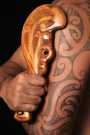 Gros plan de tamoko maori tribales tatouage et sculpté en bois simple club