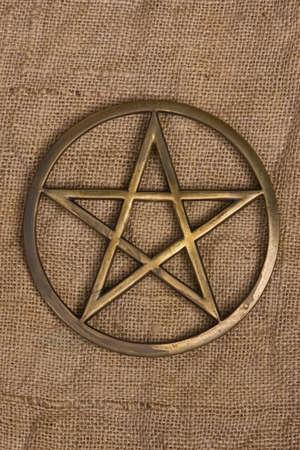 close up of brass pentagram  pentacle on burlap - hessian background Stock Photo