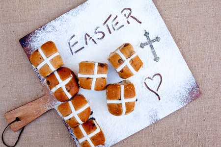 hot cross buns on floured wooden cutting board, with word Easter written in flour - with silver cross Stock Photo