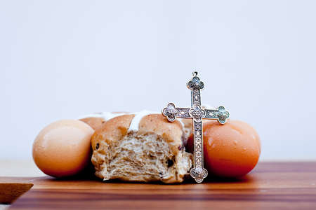 Easter - crucifix, hot cross buns and eggs on wooden cutting board Stock Photo - 79567605