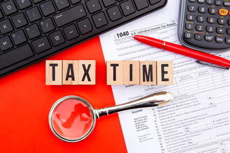 Tax Time - USA - wooden letters with 1040 Tax Form, magnifying glass, keyboard and calculator