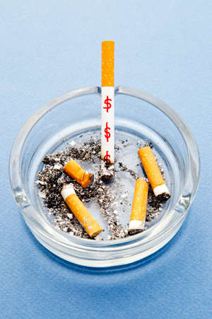 Stop Smoking - waste of money  dollars - with cigarettes and ashtray on blue background