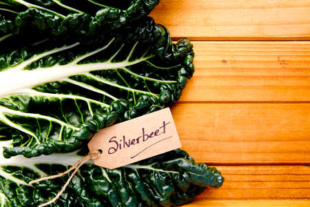 Fresh Silverbeet on wooden background - with label