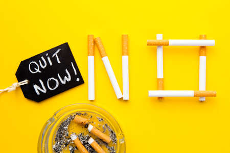 Quit Smoking - No in cigarettes with ashtray with handwritten blackboard  on yellow background