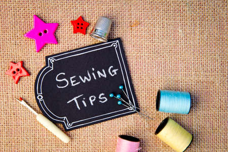 Sewing Tips on blackboard with buttons, cotton thread reels and other items on burlap background Foto de archivo