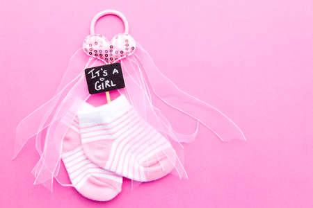 De aankondiging van het babymeisje - de roze en witte sokken met hart op roze achtergrond met het is een bord van het Meisjebord