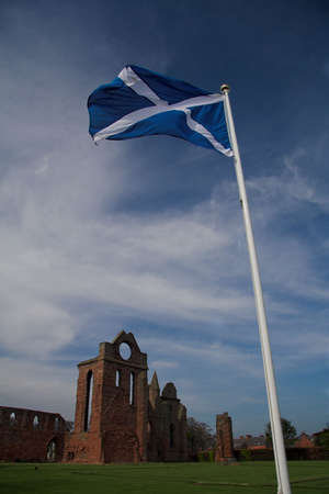 robert bruce: The saltire flag above the ruins of Arbroath Abbey where the famous Declaration was drawn up in 1320. Stock Photo
