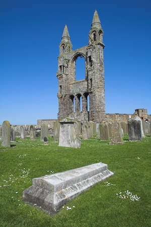 View of St Andrews Cathedral in Scotland with an ancient tombstone in the foreground. Once one of the most important religious centres in Scotland the Abbey declined after the Reformation leaving behind only these still impressive ruins.