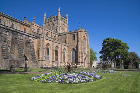 Dunfermline Abbey with a colourful flower-bed in the foreground. For centuries Dunfermline was the Scottish capital and its Abbey one of the most powerful in Scotland. All of Scotlands early medieval kings, including Robert Bruce, are entombed here.