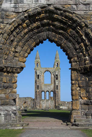 View of St Andrews Cathedral in Scotland through an ancient arched stone doorway. Once one of the most important religious centres in Scotland the Abbey declined after the Reformation leaving behind only these still impressive ruins. Stock Photo