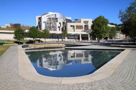 building feature: Front view of the Scottish parliament with the modern design reflected in the water feature at the front of the building.