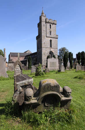 Valley Kirkyard in Stirling with a weathered 18th century monumental tombstone in the foreground and Holyrood Kirk in the background.
