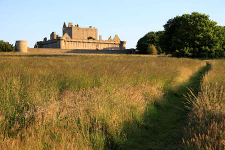 Craigmillar Castle on the outskirts of Edinburgh captured in the soft evening sunlight with a in the foreground running through a field towards the castle. Stock Photo